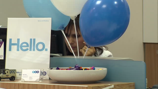 vídeos de stock, filmes e b-roll de bank returns to high street as lloyds rebrands branches clean: interiors two members of staff in new tsb branch sitting at computers tsb bank staff... - high street