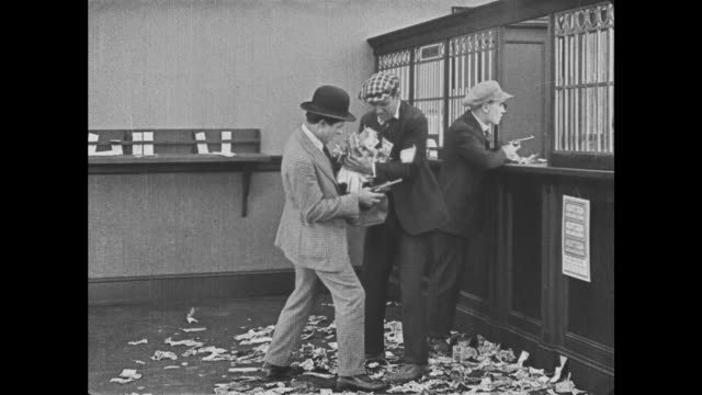 vidéos et rushes de 1921 bank robbers attempt to put sticky money into loot bag as bank teller (buster keaton) gets stuck to guns - vigilance