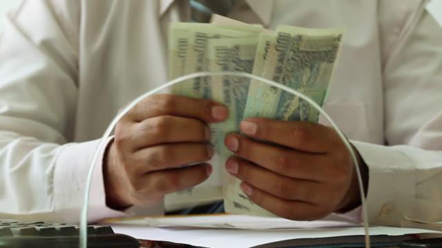 Bank Teller counting money at bank counter, Delhi, India