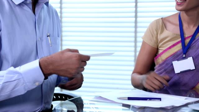bank teller giving cheqque to customer, delhi, india - scheck stock-videos und b-roll-filmmaterial