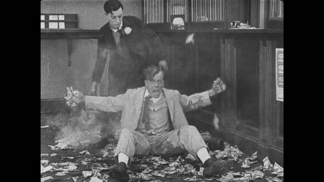 1921 bank teller (buster keaton) knocks man unconscious so he can use steaming kettle water to unstick him from bank floor - 無声映画点の映像素材/bロール