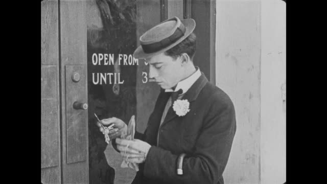 1921 Bank teller (Buster Keaton) opens bank with bottle opener before jumping over counter and proceeding to the vault