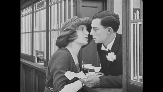 1921 bank teller (buster keaton) turns back clock for persistent bank customer (natalie talmadge) opening the vault before taking down her phone number - reversing stock videos & royalty-free footage