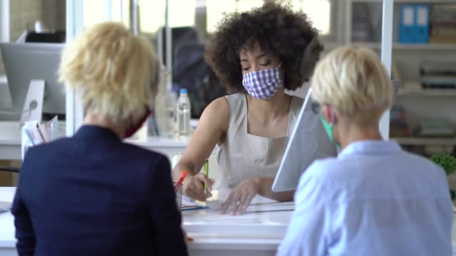 bank teller wearing protective face mask advising two female customers for signing a new contract - cashier stock videos & royalty-free footage