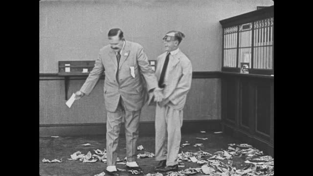 1921 bank worker (joe roberts) directs hatted man to pick money up off bank floor - messy stock videos & royalty-free footage
