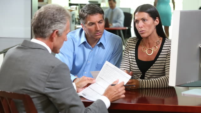 MS Banker Discussing Mortgage Application with Adult Couple in Bank / Richmond, Virginia, USA