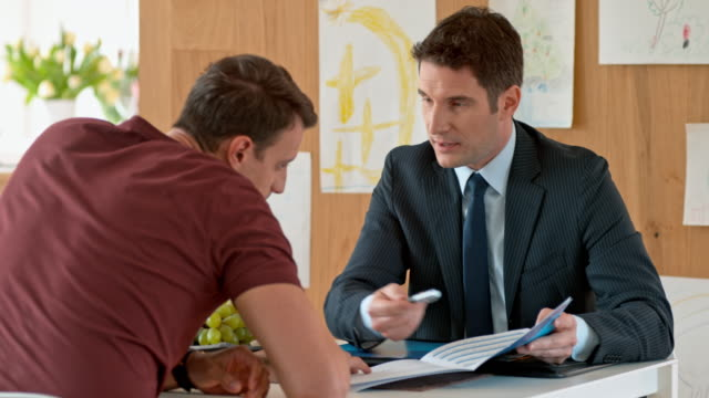 Banker explaining brochure details to Caucasian man in his home