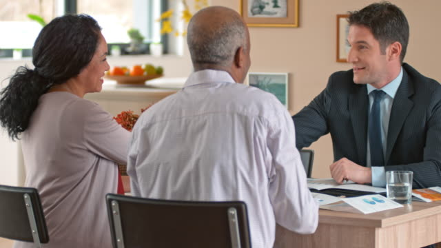 banker shaking hands with a multi ethnic senior couple at a meeting in their home - customer stock videos & royalty-free footage