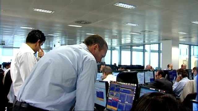 Lloyds TSB HBOS possible merger BGC trading floor Woman broker working at desk / traders standing and shouting as others work at computer screens