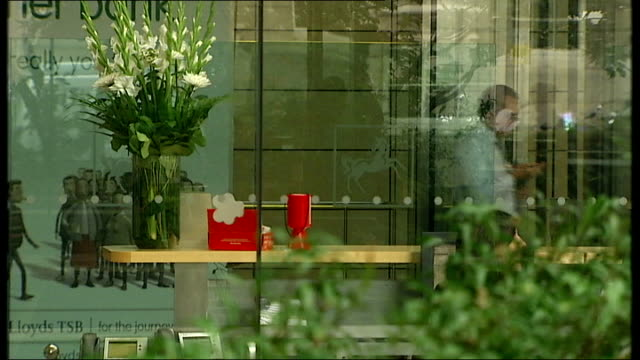 lloyds tsb hbos possible merger ext lloyds offices lloyds employee in looby seen through plate glass worker sitting at desk seen through blinds... - channel 4 news stock-videos und b-roll-filmmaterial