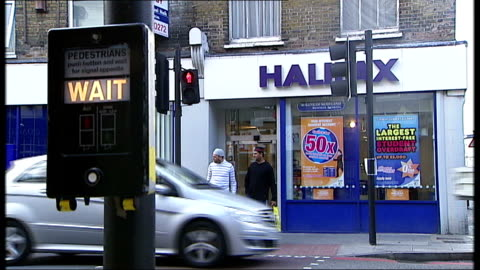 warnings ignored; t18090830 london: ext branch of halifax bank seen beyond pedestrian crossing 'wait' sign in f/g back view customer using hbos cash... - banking sign stock videos & royalty-free footage