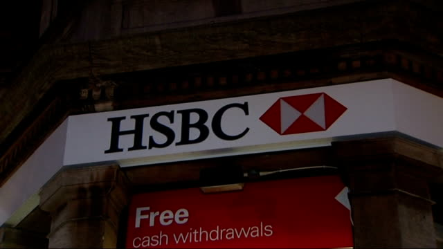 HSBC investigates nationwide system failure ENGLAND Back view of woman using ATM machine at HSBC bank branch HSBC sign on wall Man putting his credit...