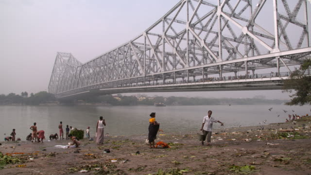 banks of hooghly river with howrah bridge in background with people - howrah bridge stock videos and b-roll footage