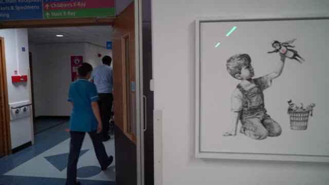 banksy artwork called game changer to recognise work of nhs during the coronavirus crisis hanging in southampton general hospital with staff looking... - hanging stock videos & royalty-free footage