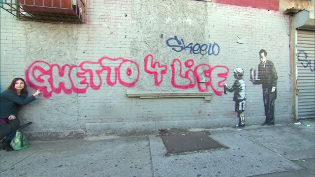 banksy inks 'ghetto 4 life' piece in south bronx on october 21 2013 in bronx new york - バンクシー点の映像素材/bロール