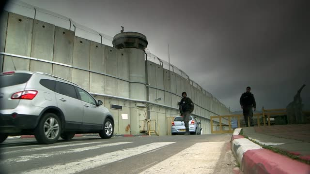 Banksy opens 'The Walled Off Hotel' in Bethlehem Bethlehem Security wall as cars along to checkpoint Graffiti on wall including the word 'Anti'...