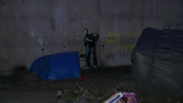 banksy 'steve jobs' graffiti artwork in calais 'jungle' migrant camp france calais migrant tents in calais 'jungle' refugee camp pan to banksy 'steve... - underpass stock videos and b-roll footage