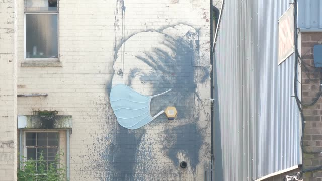 banksy street artist adds face protection to work in bristol during coronavirus pandemic - artist stock videos & royalty-free footage