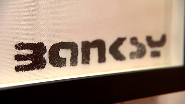banksy works exhibited at sotheby's england london sotheby's banksy paintings exhibited in room close shot banksy signature on painting close shot... - sotheby's stock videos and b-roll footage
