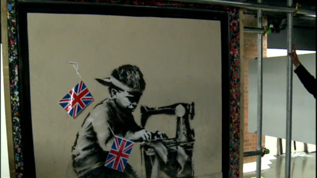 banksy's mural slave labour goes up for auction artwork and interview artwork 'slave labour' by banksy being unveiled / bunting being attached to... - バンクシー点の映像素材/bロール