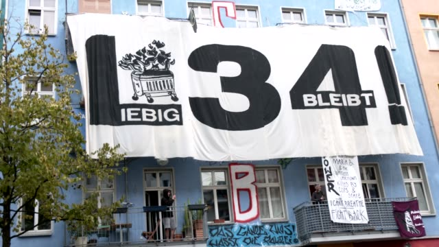 """banner at a house facade at the corner next to the building liebigstrasse 34, also known as liebig34, says """"liebig34 stays here!"""" during the eviction... - links platz stock-videos und b-roll-filmmaterial"""