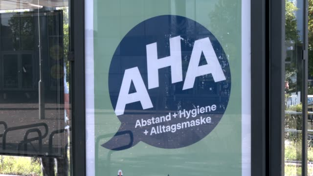 banner at a tram stop explains the aha rules distance, hygiene and protective face mask for the population to protect themselves from a covid-19... - regeln stock-videos und b-roll-filmmaterial
