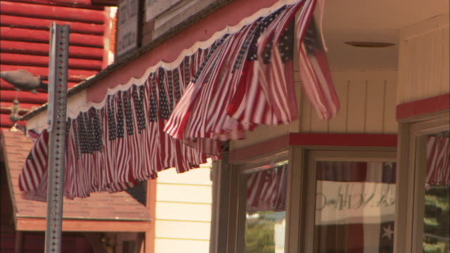 a banner of american flags flutters in the wind over a store's entrance. - ギフトショップ点の映像素材/bロール