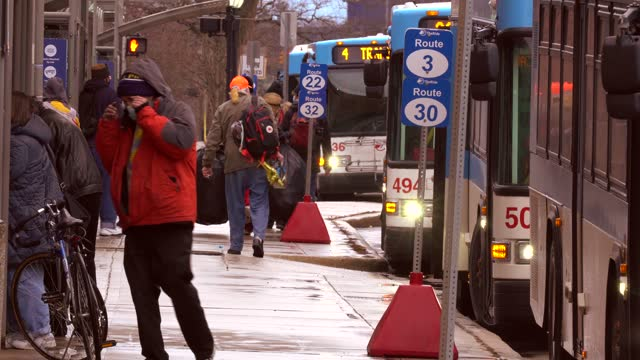 stockvideo's en b-roll-footage met banner on buses reminds passengers to only use the bus line only for essential trips on december 22 in ann arbor. during the covid pandemic, the ann... - straatnaambord