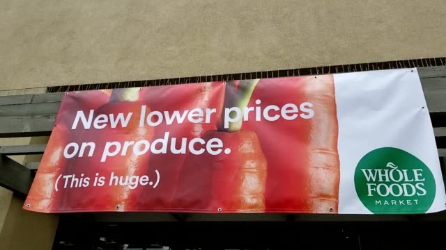 banner outside a whole foods market grocery store in san ramon california following parent company amazon's announcement that it was lowering prices... - whole foods market stock videos and b-roll footage