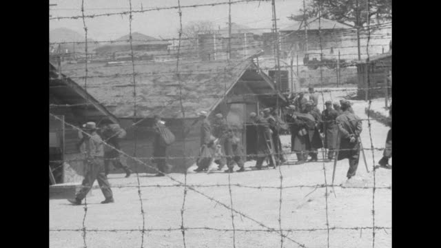 PW Camp No 2 UN Command Pusan / seen through a barbed wire fence long lines of prisoners file into barrack in Pusan / numerous men in undershirts...