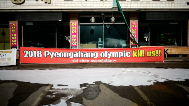 A banner protesting against the closure of ski slopes in Phoenix Park during the PyeongChang Winter Olympics hangs from a closeddown shop on February...