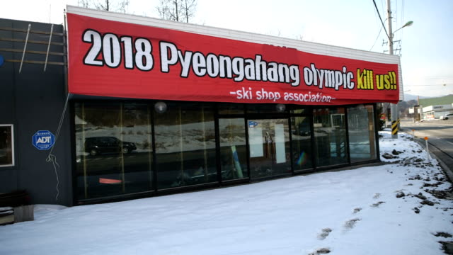 a banner protesting against the closure of ski slopes in phoenix park during the pyeongchang winter olympics hangs from a closeddown shop on february... - winter olympic games stock videos and b-roll footage
