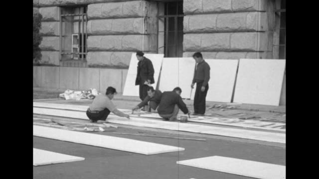 vídeos de stock, filmes e b-roll de banner reading welcome presidentelect eisenhower stretched across road leading to city hall / korean men painting signs lying on ground / banner... - edifício do governo local