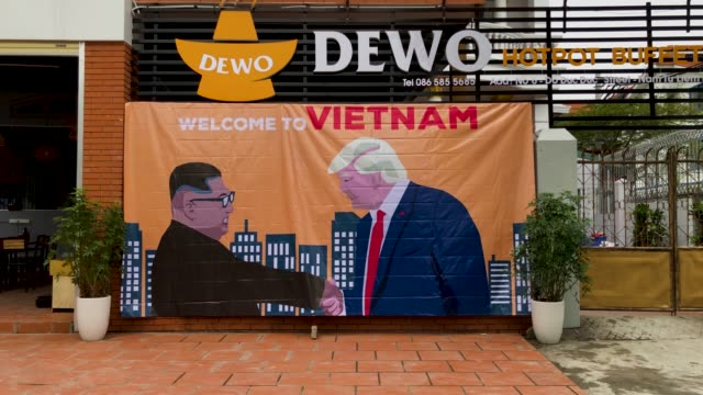 a banner showing us president donald trump and north korean leader kim jongun shaking hands next to the words 'welcome to vietnam' hung opposite the... - 首脳会議点の映像素材/bロール