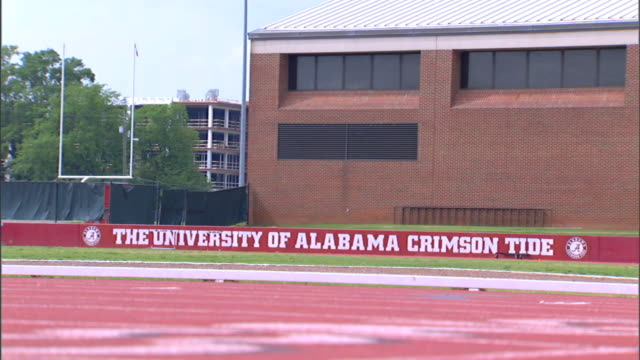 Banner sign behind track The University of Alabama Crimson Tide brick building w/ wrapped fencing w/ goal post beyond
