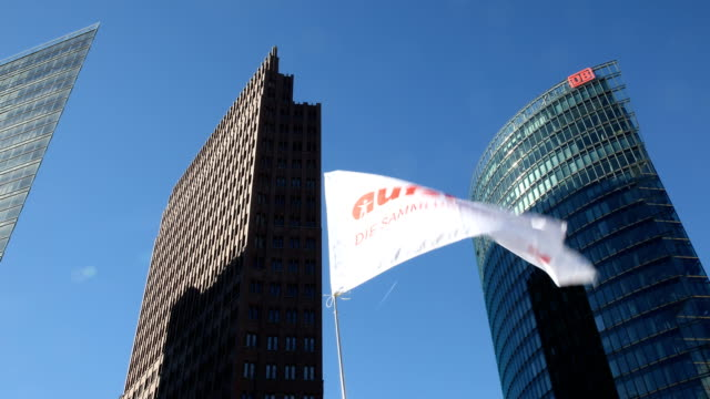 """banner """"stand up"""" - the collection movement"""" in the foreground, in the background a blue sky and skyscrapers at potsdamer platz can be seen.... - links platz stock-videos und b-roll-filmmaterial"""