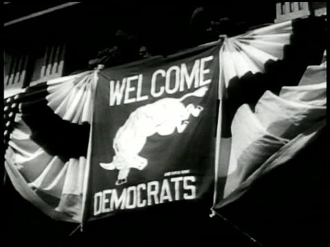 stockvideo's en b-roll-footage met banner w/ bull drawing 'welcome democrats' la ms banner w/ elephant drawing 'welcome gop' ha ws large crowd at philadelphia presidential convention... - 1948