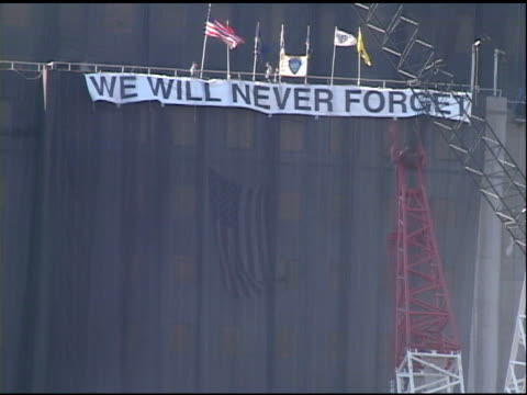 banner we will never forget hangs on roof of shrouded building over ground zero with electronic flag god bless america sign - attentati terroristici dell'11 settembre 2001 video stock e b–roll