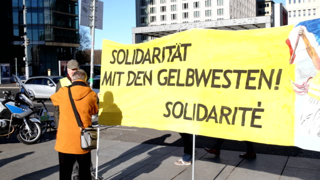 """banner with the inscription: """"solidarity with the yellow vests."""" supporters of the new left-wing """"stand up"""" movement gather at a demonstration at... - links platz stock-videos und b-roll-filmmaterial"""
