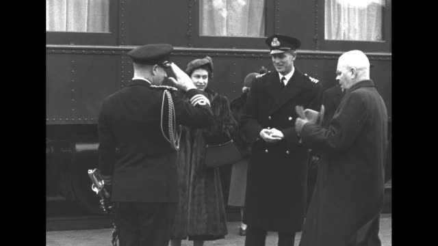 'Welcome to Regina' / Elizabeth wearing a fur coat steps from train and is greeted by dignitary / Prince Philip is greeted by military officer / VS...