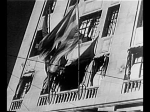stockvideo's en b-roll-footage met banners on building in barcelona during spanish civil war / building with tattered catalan flag fluttering with other flag / cu generalissimo... - burgeroorlog