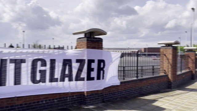 banners outside manchester united's old trafford stadium, protesting against owners, the glazer family - information medium stock videos & royalty-free footage
