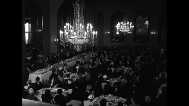 Banquet hall with chandeliers and waiters / document 'Mr Eric Johnston Award of Merit'