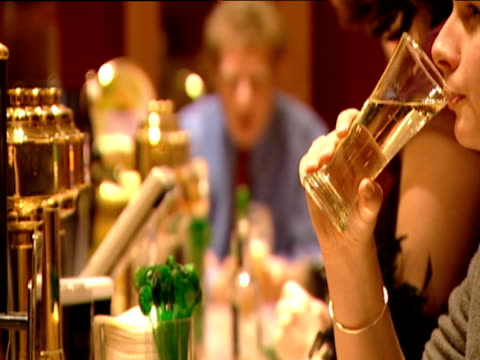 bar activity in a pub includes beer pumps people ordering and drinking and wine being poured into a wine glass - ワインバー点の映像素材/bロール