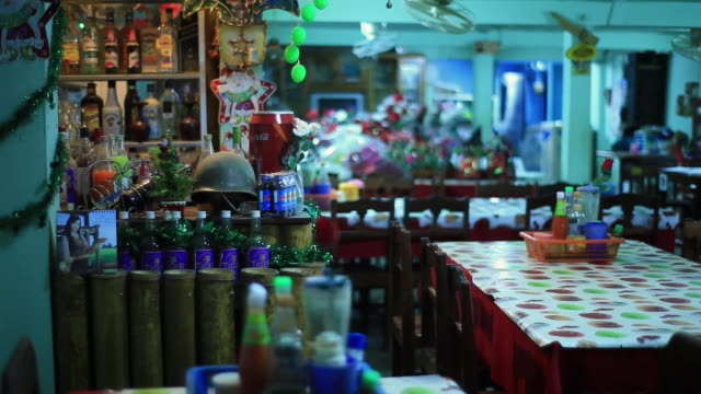ms bar area of small restaurant with ecclectic mix of decorations including  miniature christmas tree and army helmet with different colored liquids bottles /  vang vieng, vientiane, laos - army helmet stock videos & royalty-free footage
