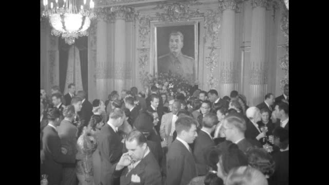 Bar in packed embassy room / people under large portrait of Joseph Stalin / VS blinking light in ice sculpture and guests eating caviar / VS busy...