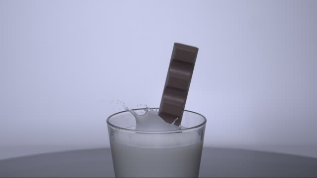 bar of chocolate is falling into a glass of water