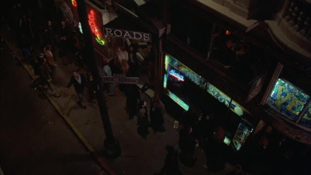 Bar patrons and pedestrians crowd the sidewalk outside a bar entrance.