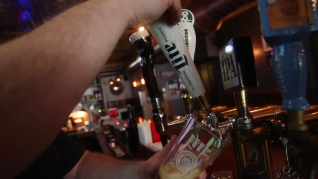 a bar tender pours a glass of miller high life beer at a bar on october 9 2015 in new york city budweiser's parent company ab inbev is attempting to... - アンハイザー・ブッシュ・インベブ点の映像素材/bロール