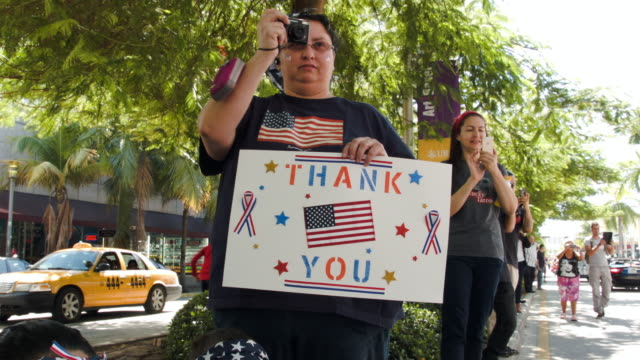 barabara rodriguez holds a sign that reads 'thank you' as she watches the parade march past during the miami beach veterans day ceremony on november... - armistice day stock videos and b-roll footage